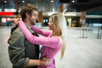 Pareja alegre abrazándose en la sala de espera en la terminal del aeropuerto - foto de stock
