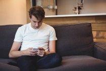 Hombre sentado en el sofá utilizando el teléfono móvil en la sala de estar en casa - foto de stock