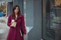 Donna d'affari in possesso di tazza di caffè usa e getta, pacco e diario camminare sul marciapiede — Foto stock