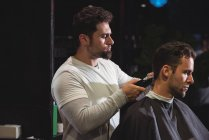 Man getting hair trimmed by barber with trimmer in barber shop — Stock Photo