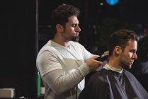 Hombre conseguir pelo recortado por barber con barbero en la barbería - foto de stock
