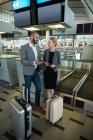 Empresários segurando cartão de embarque e usando telefone celular no terminal do aeroporto — Fotografia de Stock
