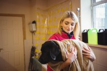 Woman holding dog in bath towel at dog care center — Stock Photo
