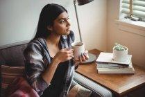 Женщина с чашкой кофе смотрит в окно дома — стоковое фото