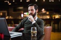 Uomo guardando computer portatile al bar interno — Foto stock