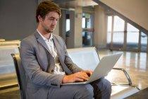 Uomo d'affari che lavora al suo portatile nella sala d'attesa del terminal dell'aeroporto — Foto stock