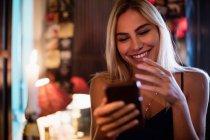 Bella donna sorridente utilizzando il telefono cellulare nel bar — Foto stock