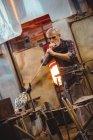 Soffiatore di vetro che modella un vetro sul blowpipe alla fabbrica di soffiaggio del vetro — Foto stock