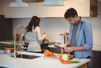 Hombre para picar las verduras en la cocina al cocinar los alimentos en fondo en la casa de la mujer - foto de stock