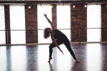 Молодая женщина, практикующая современный танец в танцевальной студии — стоковое фото