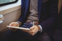 Mid-section of businessman holding digital tablet while travelling in train — Stock Photo