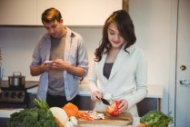 Woman chopping vegetables and man using mobile phone in the kitchen at home — Stock Photo