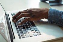 Primer plano de la mano del ejecutivo de negocios utilizando el ordenador portátil en la oficina - foto de stock