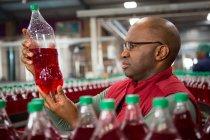 Серьезный работник мужского пола осматривает бутылку на заводе холодных напитков — стоковое фото