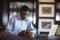 Homme d'affaires utilisant le téléphone portable dans le bureau — Photo de stock
