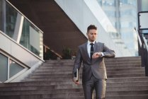 Empresário verificando o tempo enquanto desce escadas no escritório — Fotografia de Stock