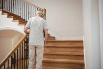 Un aîné monte les escaliers à la maison — Photo de stock