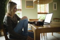 Woman using laptop while sitting in living room at home — Stock Photo
