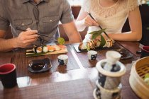 Mid section of couple having sushi in restaurant — Stock Photo