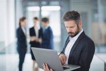Empresario de pie en la oficina y el uso de ordenador portátil - foto de stock