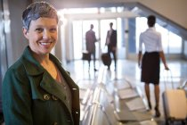 Portrait of woman smiling at airport terminal — Stock Photo