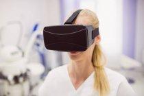 Médecin féminin portant un casque de réalité virtuelle en clinique — Photo de stock