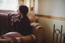 Задумчивая женщина сидит и держит чашку кофе дома — стоковое фото