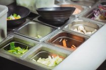 Trays of various chopped vegetables in kitchen of restaurant — Stock Photo