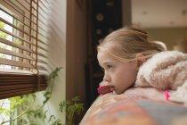 Chica pensativa mirando a través de la ventana en la sala de estar en casa - foto de stock