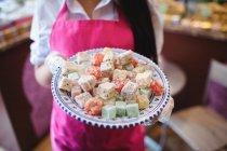 Розділ середині жіночий крамар проведення лоток Турецька солодощі в лічильника в магазин — стокове фото