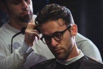 Uomo ottenere capelli tagliati dal barbiere con trimmer in negozio di barbiere — Foto stock