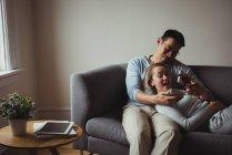 Hombre dando regalo sorpresa a su mujer en el sofá en casa - foto de stock
