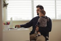 Father holding his baby while using laptop at desk at home — Stock Photo
