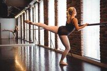 Ballerine pratiquant la danse de ballet à la barre dans le studio de ballet — Photo de stock