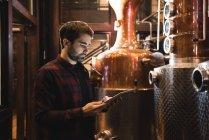 Людина, використовуючи цифровий планшетний у пивоварний завод — стокове фото