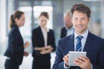 Portrait d'un homme d'affaires utilisant une tablette numérique au bureau — Photo de stock