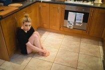 Задумчивая женщина сидит дома на кухне — стоковое фото
