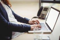 Sección media de la mujer de negocios embarazada usando el ordenador portátil en la oficina - foto de stock