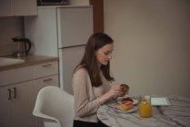 Женщина держит кекс во время завтрака дома — стоковое фото