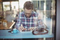 Young man using digital tablet in cafeteria — Stock Photo