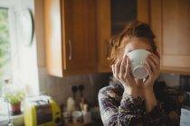 Donna che prende il caffè in cucina a casa — Foto stock
