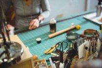 Различные инструменты работы на столе в мастерской с женщиной, работающей в фоновом режиме — стоковое фото