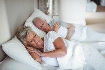 Pareja mayor durmiendo en la cama en el dormitorio - foto de stock