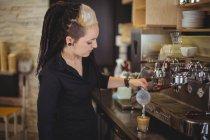 Официантка наливает молоко в кофейную чашку у стойки в кафе — стоковое фото