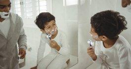 Père et fils se rasant ensemble dans la salle de bain à la maison — Photo de stock