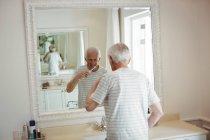 Старший чоловік чистити зуби у ванній кімнаті — стокове фото
