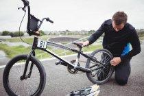 Велогонщик ремонтирует велосипед BMX в скейтпарке — стоковое фото