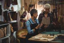 Ремесленницы обсуждают за кожаной сумкой в мастерской — стоковое фото