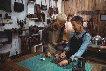 Ремесленницы обсуждают за куском кожи в мастерской — стоковое фото