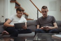Two men using digital tablet and mobile phone in living room at home — Stock Photo